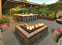L Shaped Natural Stone Firepit With An Outdoor Kitchen