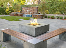 Modern firepit with bench seating and natural stone water feature
