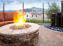Natural Stone Circular Firepit With A Water Feature And Seating