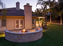 Natural Stone Circular Firepit With A Stone Wall And Turf